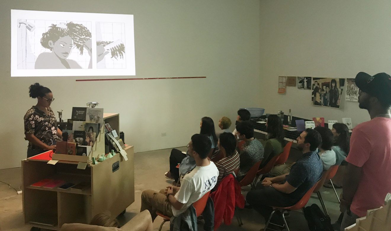 jamila rowser reading her comic, Wash Day in front of a crowd of people