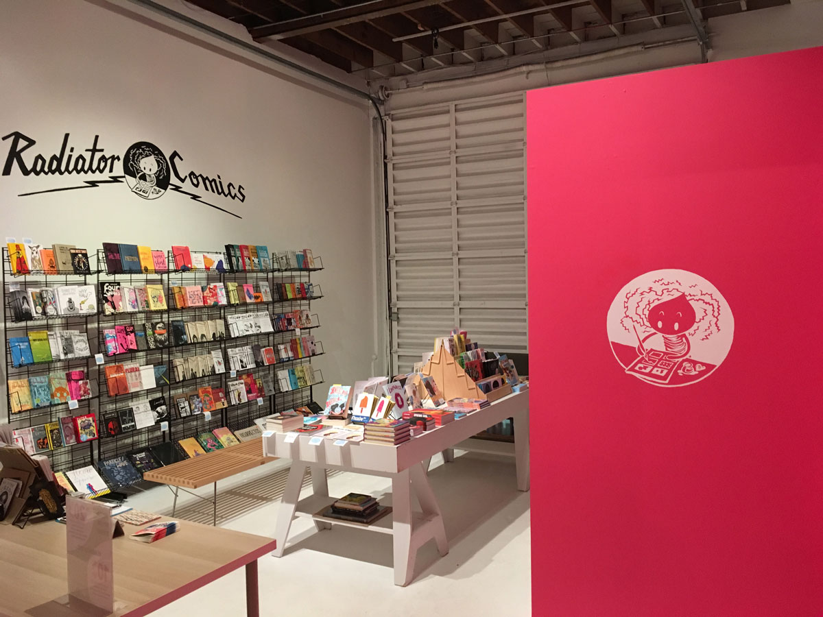 shelves filled with comics, a bright magenta wall with the Radiator Comics logo in white